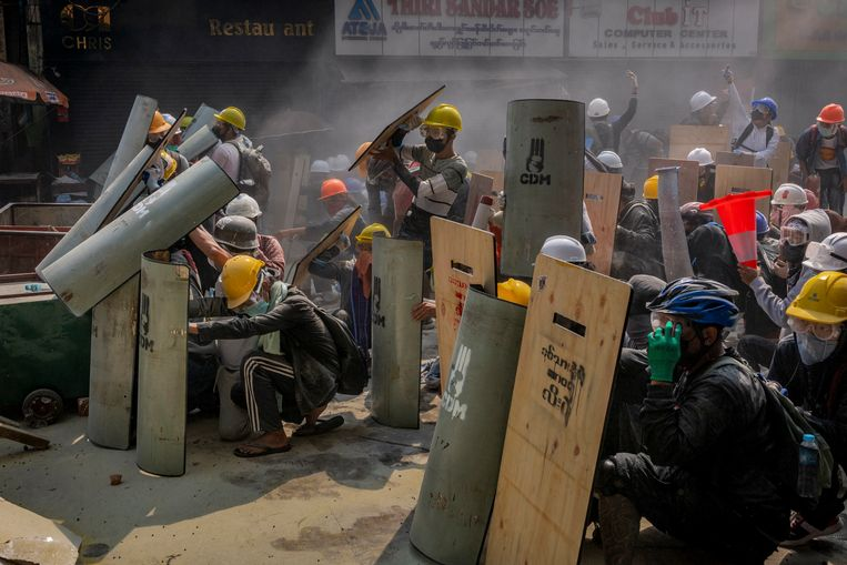 Demonstranten in Yangon beschermen zichzelf tegen de politie.  Beeld Getty Images