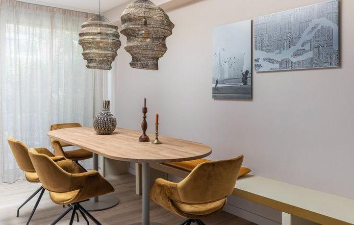 Als je aan de lange zijde een bank maakt, kun je de tafel wat naar de zijkant schuiven. Styling Fietje Bruijn.