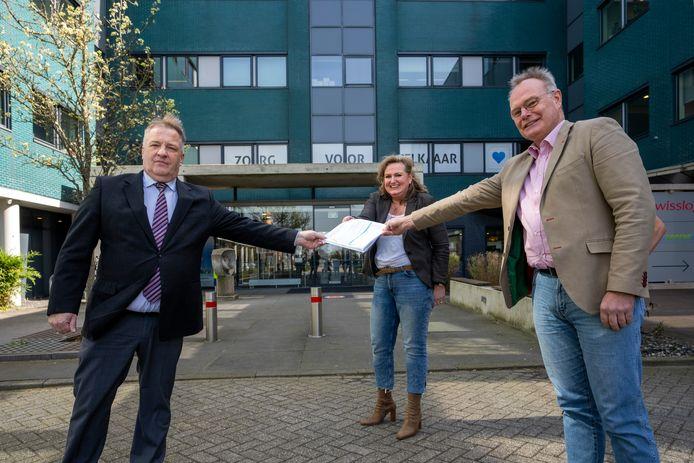 Koos de Looff (rechts) van de Vereniging Vestingstad Zaltbommel overhandigt de door ruim 1100 inwoners ondertekende petitie aan loco-burgemeester Adrie Bragt en griffier Monique Muurling.