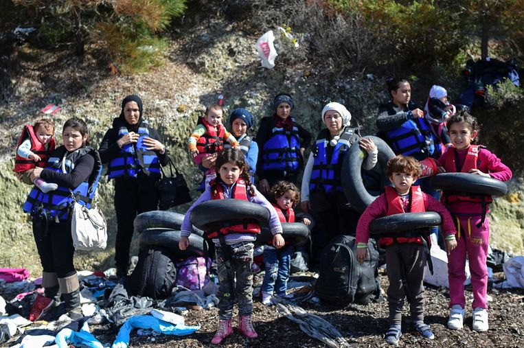 In de Turkse kustplaats Canakkale dragen migranten reddingsvesten voor de tocht naar Griekenland, eind februari 2016. Beeld Bulent Kilic/AFP