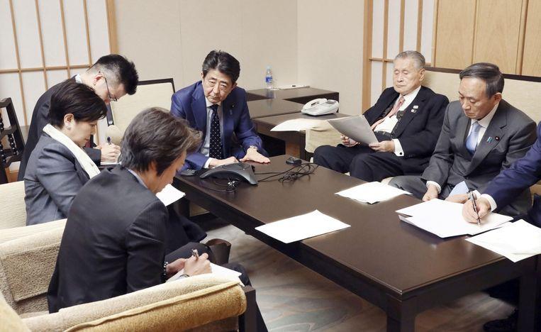 De Japanse premier Shinzo Abe zit aan het hoofd van de tafel. Ook Yoshiro Mori (olympisch organisatiecomité), Yuriko Koike (gouverneur Tokio), Seiko Hashimoto (minister Olympische Zaken) en Yoshihide Suga (kabinetsmedewerker) zijn aanwezig op de meeting. Beeld via REUTERS