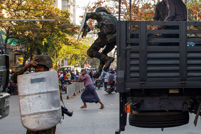 Een man rent weg terwijl militairen uit een truck springen tijdens een demonstratie tegen de coup in Mandalay.  Beeld AFP