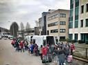 Arbeidsmigranten stappen, nadat ze op Eindhoven Airport zijn aangekomen, in busjes langs de Freddy van Riemsdijkweg.