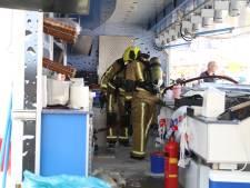 Brandweer blust vuur in viskraam