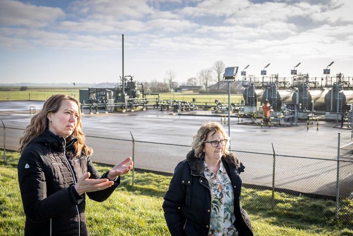 """Rita Pos en Marijke Sterk, bij de draaiende gaswininstallatie in Eesveen. Ze willen dat die het zwijgen op wordt gelegd. ,,Wij vinden dat het hier te hard van stapel loopt."""""""