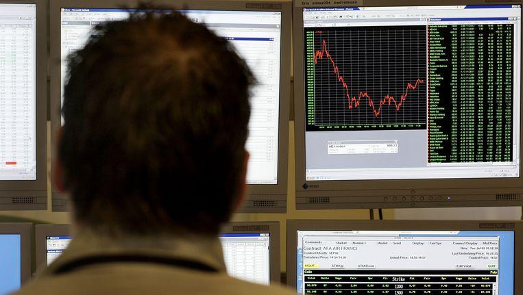 Een handelaar kijkt op het scherm naar een AEX-index die volledig in het rood staat (archieffoto). Beeld anp
