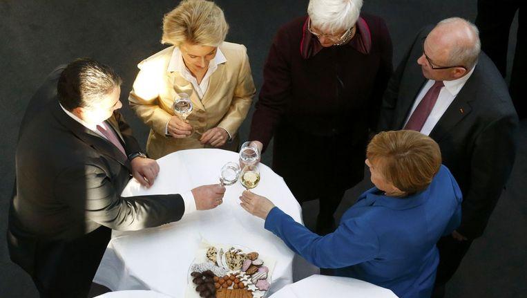 Agnela Merkel (blauw jasje) proost met politici van de CDU en CSU op het tekenen van het regeerakkoord met de SPD. Beeld reuters
