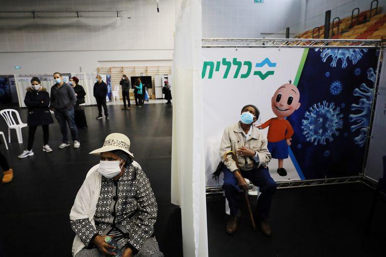Een vrouw wacht op haar vaccinatie, een ander zit even bij te komen na het hebben gekregen van de prik in het Israëlische Petah Tikva.  Beeld REUTERS