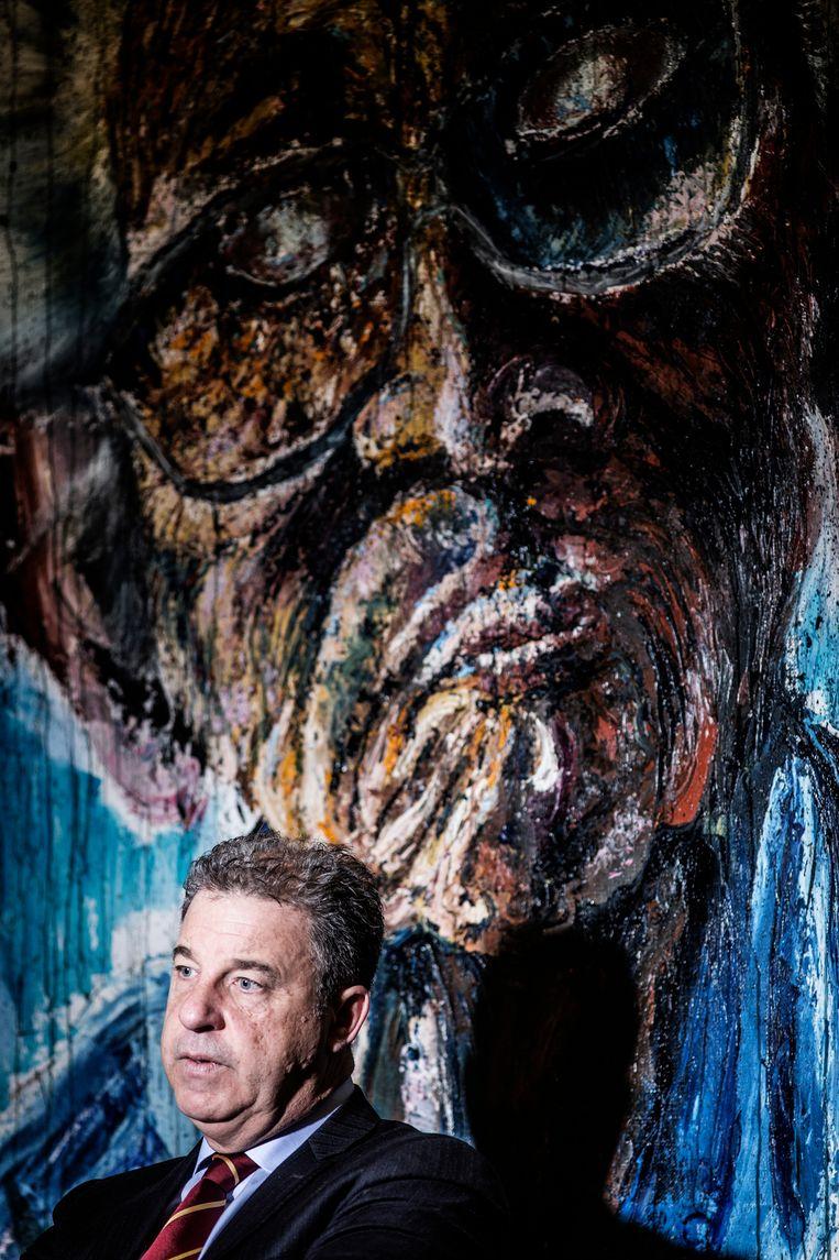Brammertz in zijn bureau in Den Haag. Achter hem een geschilderd portret van een slachtoffer van de burger-oorlog in Sierra Leone. 'Ook wat daar is gebeurd, mogen we nooit vergeten.'  Beeld Franky Verdickt