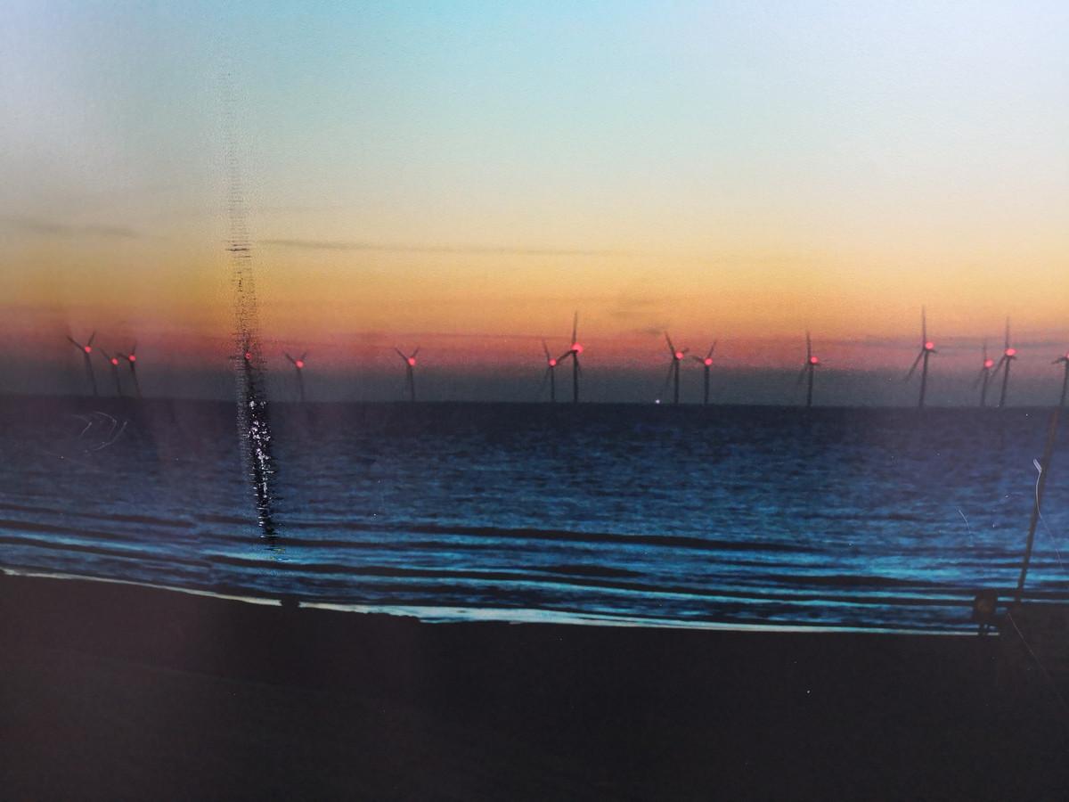 Een conceptbeeld van het geplande windmolenpark bij valavond.