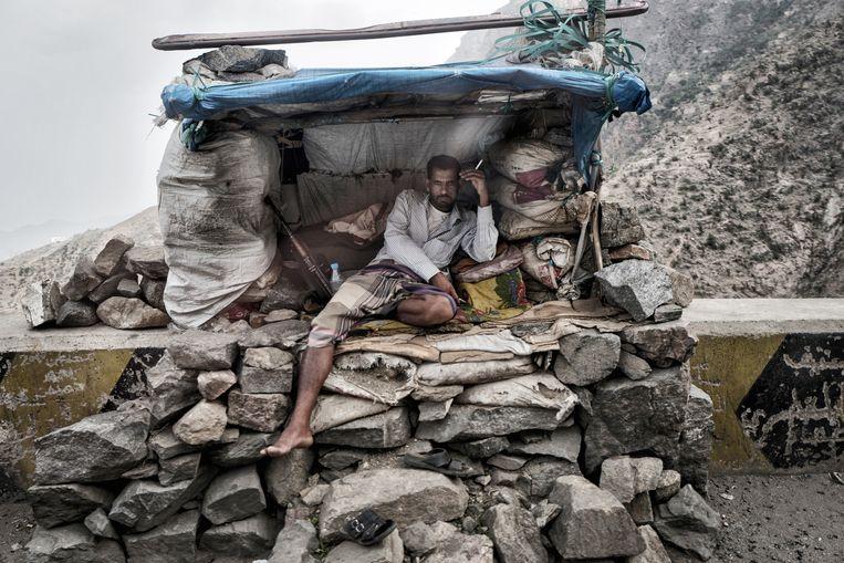 Een strijder staat op de wacht naast de weg naar Aden.  Beeld Olivier Laban-Mattei / MYOP