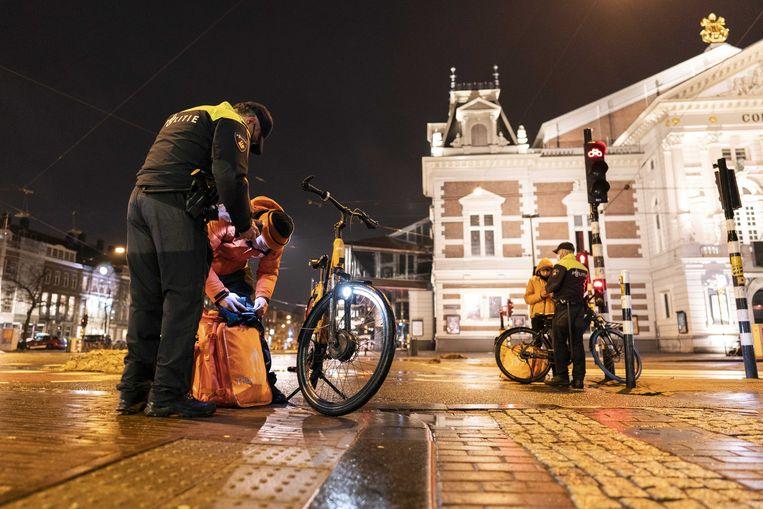 De politie controleert dinsdagavond tijdens de avondklok op het Museumplein in Amsterdam. De avondklok blijft voorlopig van kracht.  Beeld ANP