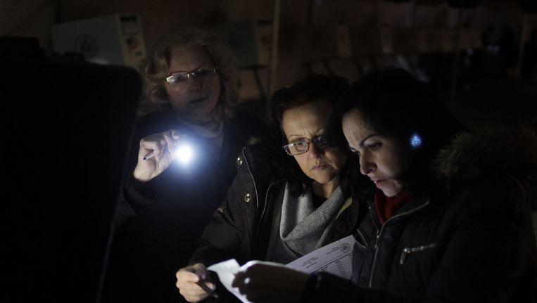 In het New Yorkse stadsdeel Staten Island proberen medewerkers van een stembureau een stemmachine aan de praat te houden. De school waarin het stembureau zou worden gehuisvest, werd vorige week verwoest door superstorm Sandy. Beeld ap