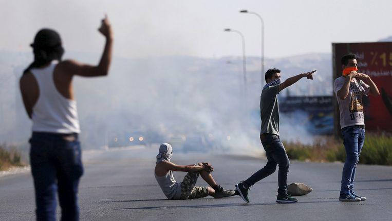 Palestijnse jongeren maken gebaren naar Israëlische veiligheidstroepen tijdens de protesten. Beeld reuters