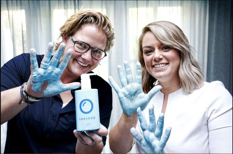 Michelle Peters (links) laat haar blauwe handen zien na gebruik van Seesoap.  Beeld