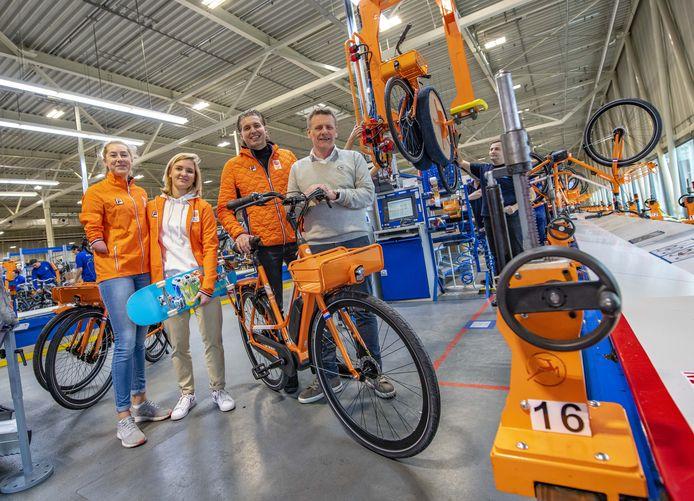 Noëlle Roorda, Roos Zwetsloot en Pieter van den Hoogenband ontvangen de eerste oranje Gazellefiets in de fietsenfabriek van Gazelle van directeur Huub Lamers.