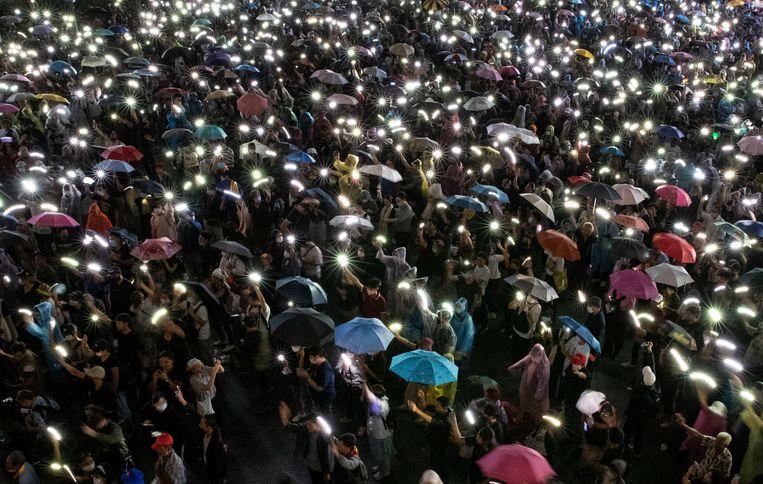 Betogers laten donderavond massaal de lichtjes van hun mobieltjes schitteren bij een grote demonstratie voor meer democratie in Bangkok. Beeld AP