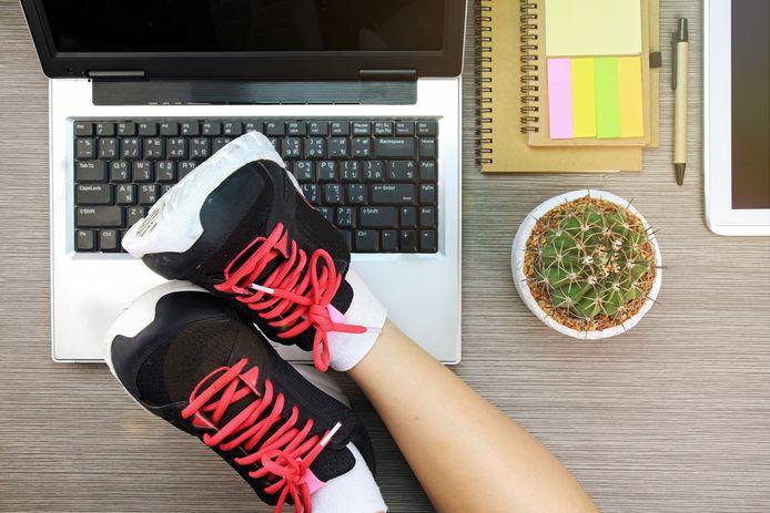 Een vrouw legt haar voeten op haar bureau. Foto ter illustratie.