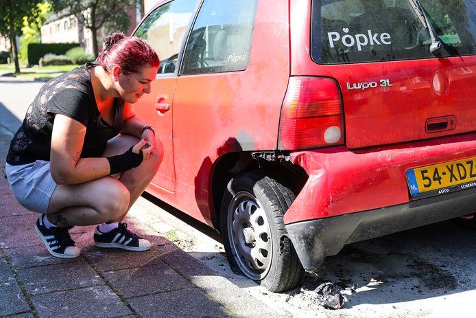 Judit bij de linker achterband van haar Volkswagen Lupo die afgelopen nacht in brand vloog.