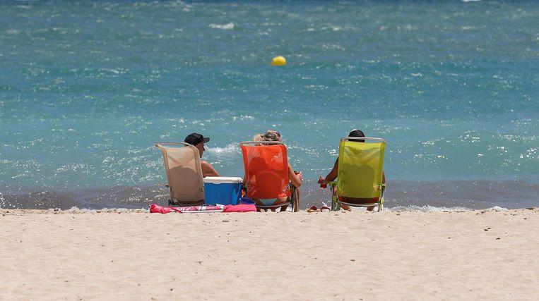 Zonnebadende toeristen bij het strand van Magaluf, in Palma de Mallorca, Spanje. Beeld Reuters