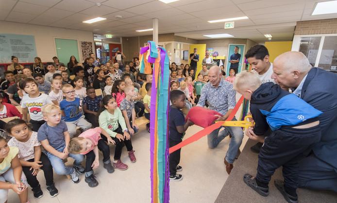 Bij de opening van het schooljaar bij Step! knippen kinderen samen met wethouder Alex Langius (rechts) een lintje door. In het midden directeur Rob Rijnbeek.
