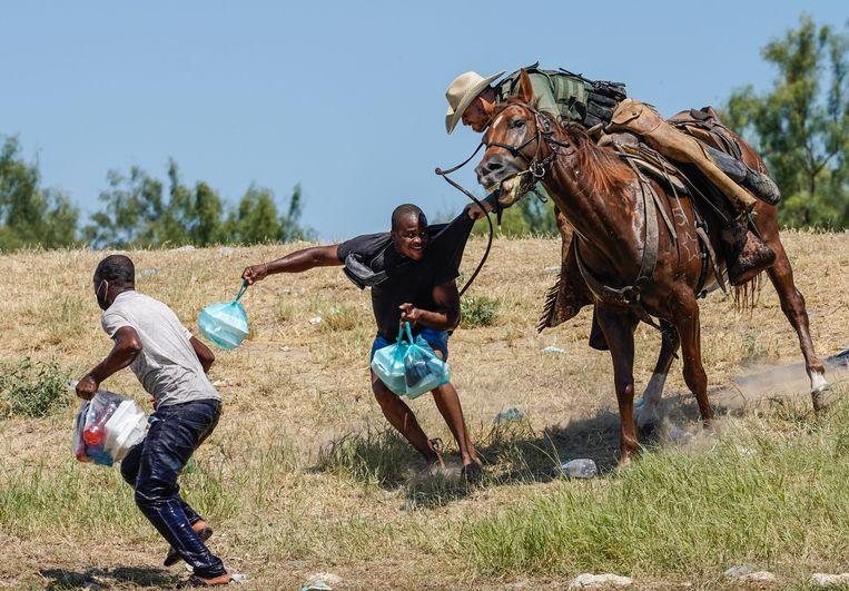 Een grenswachter te paard probeert een Haïtiaanse vluchteling tegen te houden.  Beeld AFP