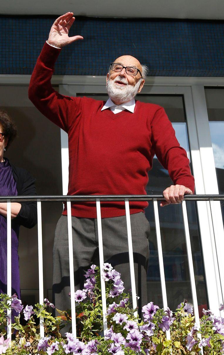 François Englert juicht op het balkon van zijn woonst in Brussel. Beeld REUTERS