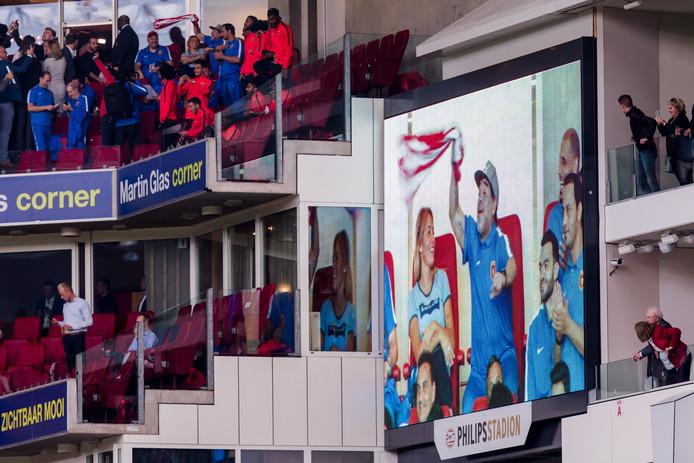 Diego Maradonna maakt de PSV-supporters gek om met een PSV-shirt te zwaaien. Fans zien dat op grote schermen.