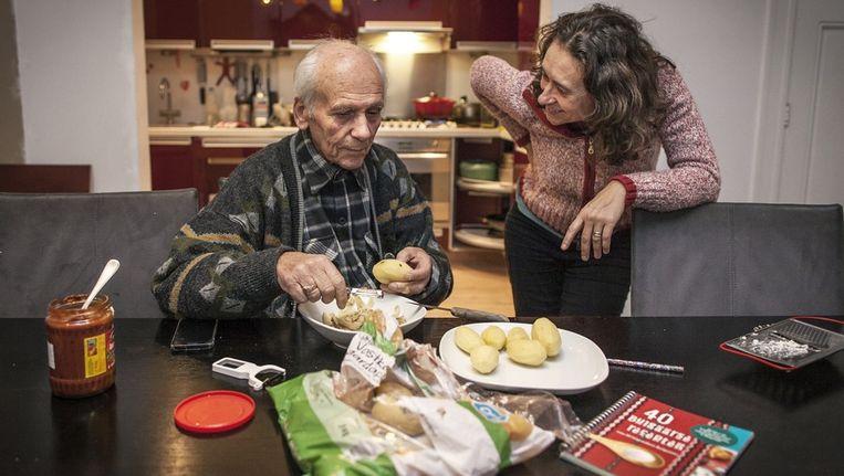 De vader van Dessi schilt aardappels voor de patat met Bulgaarse kaas. Beeld Marc Driessen / www.marcdriessen.nl