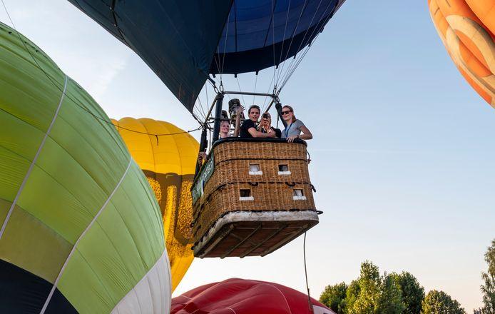 Een groot aantal luchtballonnen stijgt op vanaf een grasveld naast de brouwerij in Oijen.