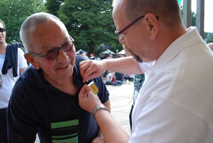 Henk Frankevijle krijgt zijn Vierdaagsekruisje opgespeld.