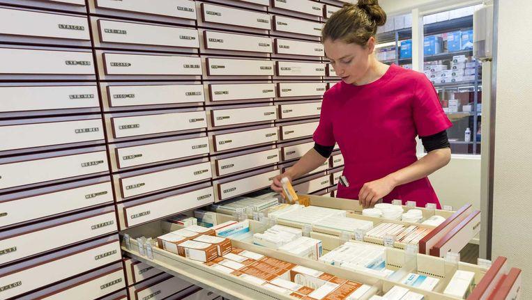 Een apothekersassistente zoekt medicijnen bij elkaar. Beeld anp