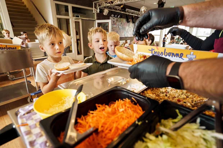 Leerlingen van De Wijde Wereld in Uden halen hun lunch op in de kantine.