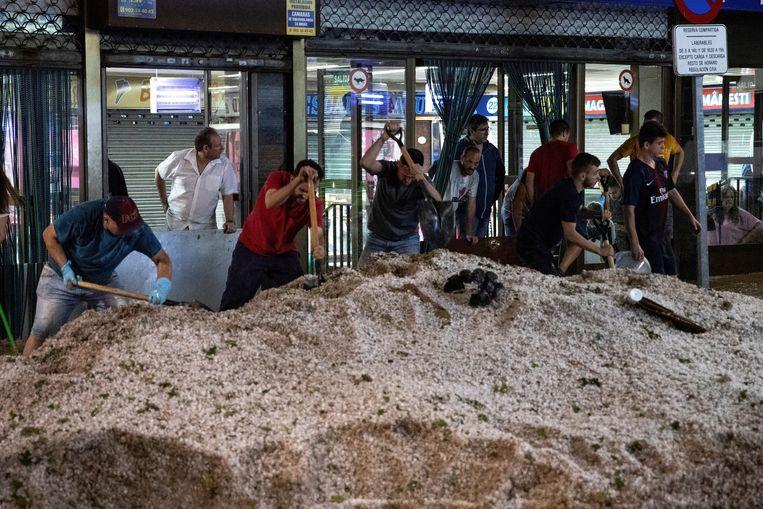 Bewoners proberen in voorstad Arganda del Rey de hagelsmurrie te verwijderen.