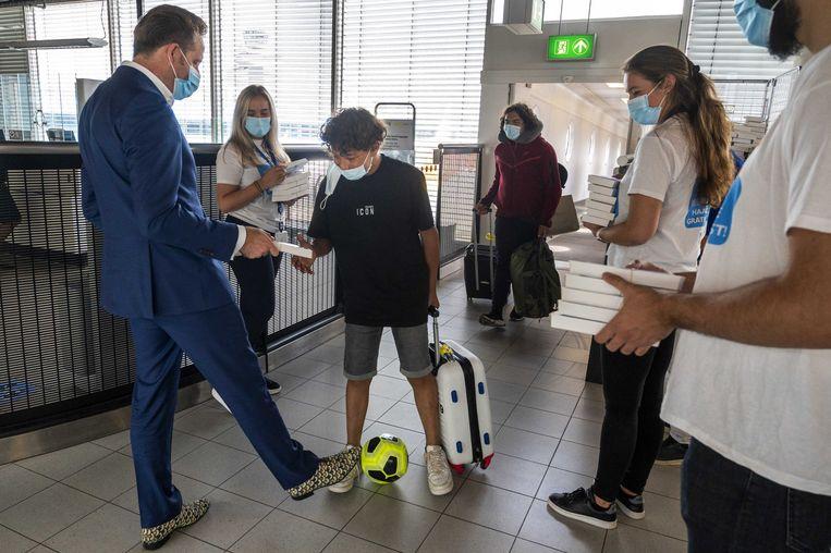 Demissionair minister Hugo de Jonge (Volksgezondheid) deelt samen met de GGD Kennemerland zelftesten uit aan jongeren die terugkeren van vakantie. Beeld ANP