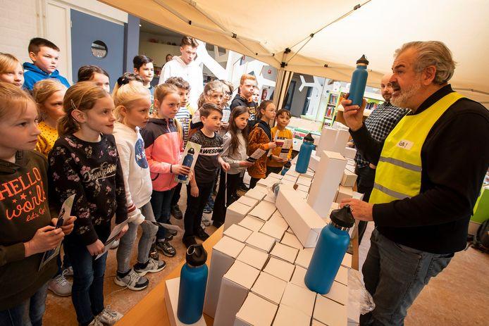 Rob van Holstein van stichting Cleanup Team Westland deelt de blue bottles uit aan de leerlingen van basisschool De Vlieten in De Lier.