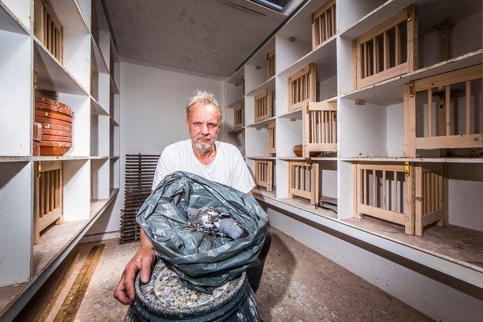 Hendrie ter Meer in een leeg duivenhok, met een plastic zak waarin circa 50 dode duifjes zitten.