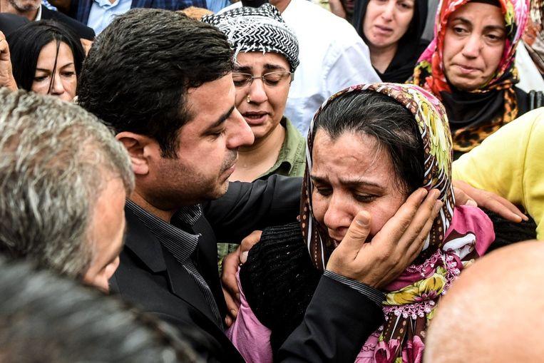 Selahattin Demirtas troost een nabestaande van een van de slachtoffers van de aanslag in Ankara. Beeld afp