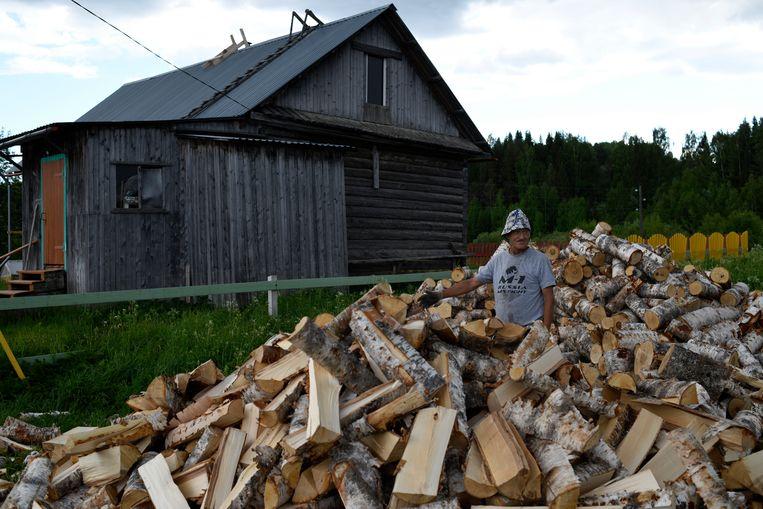 Een man in Kyltovo, in de provincie Komi, toont zijn voorraad voor de winter. 93 procent van de dorpen in Komi heeft geen gas.  Beeld Yuri Kozyrev/Noor