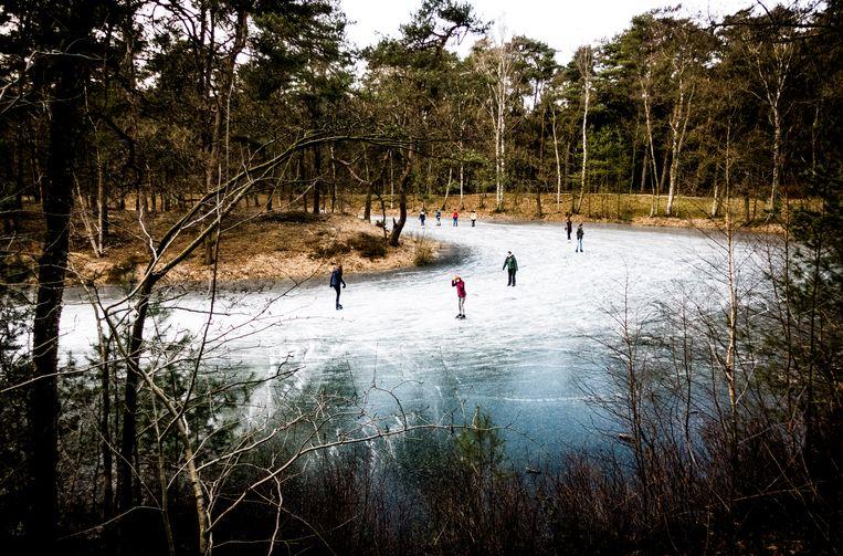 Op landgoed Heidestein, bij Driebergen, schaatsen mensen op een meertje in het bos.  Beeld Freek van den Bergh / de Volkskrant