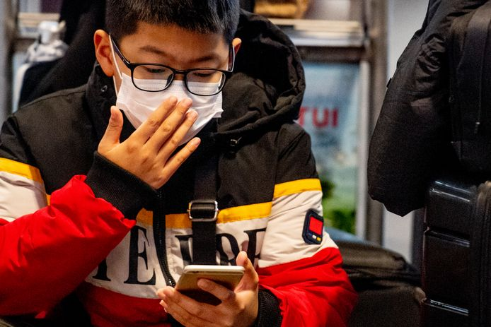 Reizigers op Schiphol met mondkapjes op ter bescherming