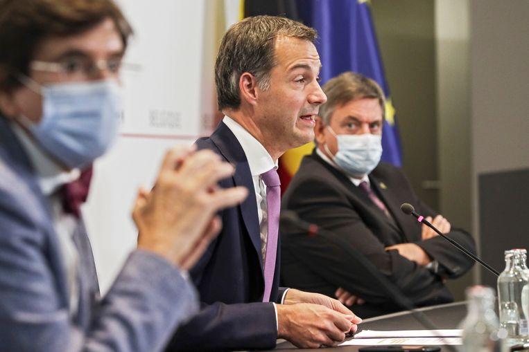 Premier Alexander De Croo (Open Vld) tussen Vlaams minister-president Jan Jambon (N-VA) en Waals minister-president Elio DI Rupo (PS). Beeld Photo News
