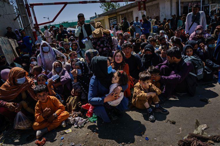 Vrouwen en kinderen moeten wachten bij een checkpoint van de Taliban in de buurt van het vliegveld van Kabul, op 25 augustus 2021.  Beeld Los Angeles Times via Getty Imag