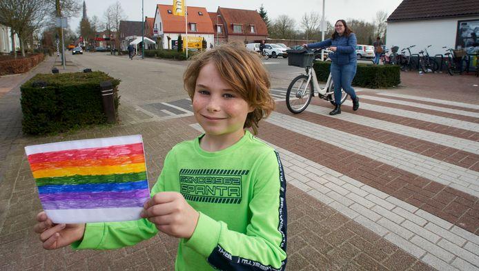 Ferre Otjens (7 jaar) voert actie om van het zebrapad aan de Sint-Servatiusstraat in Heeswijk Dinther een regenboogvariant te maken. Op de foto bij het huidige zebrapad met zijn ontwerp. Moeder Linda steekt over.