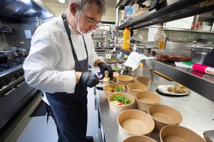 Chef-kok Marco Romviel van het Wijchense restaurant Sterrebosch maakt talloze afhaalbakjes met een duo van zeebaars en zalm klaar. Het loopt dit weekend storm qua bestellingen in de horeca.