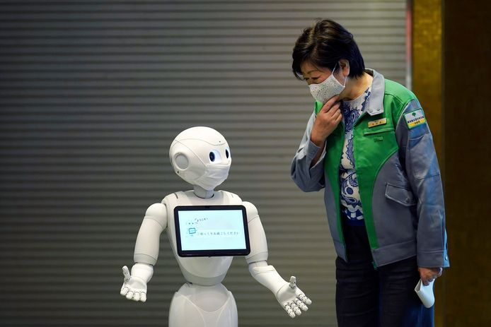 Een Pepper-robot begroet een voorbijganger.
