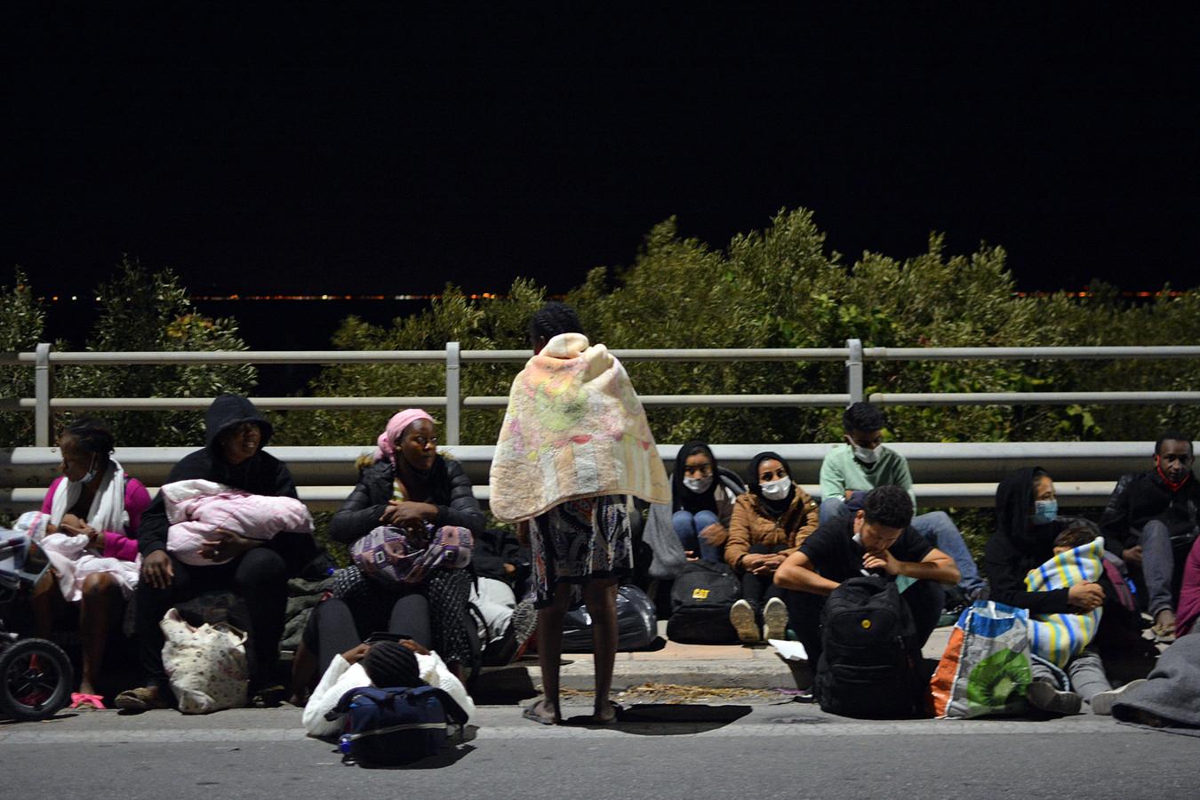 Door de brand ontheemde asielzoekers wachten op wat komen gaat langs een weg op het eiland Lesbos.