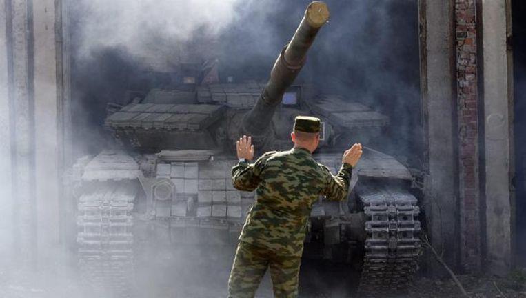 Een tank van de pro-Russische rebellen wordt in een hangar bij Loehansk gereden. Beeld EPA