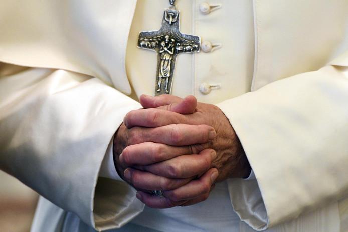 Paus Franciscus vouwt devoot de handen