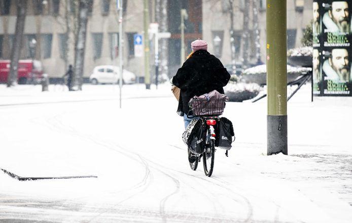 Een vrouw fietst door de sneeuw in wit Den Haag.